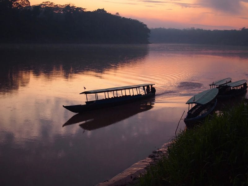 A boat navigating the Tambopata river during sunrise in the Amazon rainforest in Peru.