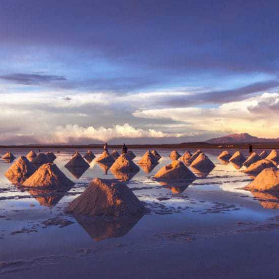 Uyuni salt flats. Piles of salt scattered throughout the puddled field with a colorful sunset which is reflecting off the salt field flats