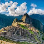 A view facing Machu Pichu in the Peruvian Andes with a blue sky and pearly white clouds