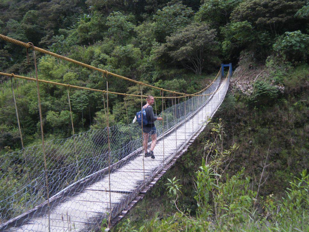 Inca Jungle Trail - Hiker crossing rickety footbridge.
