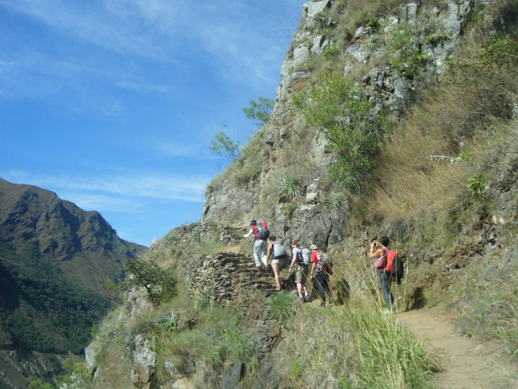 Inca Jungle Trail - A line of trekkers head up a narrow mountainside path.