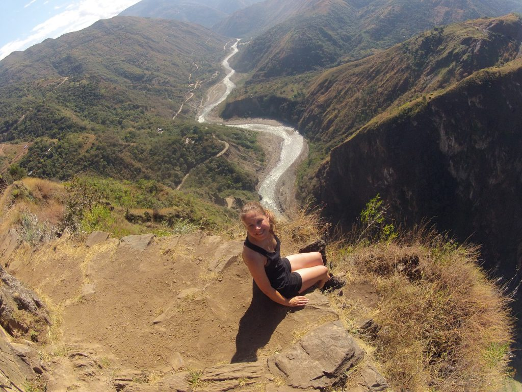 Inca Jungle Trail - Hiker on cliff ledge with spectacular views behind.