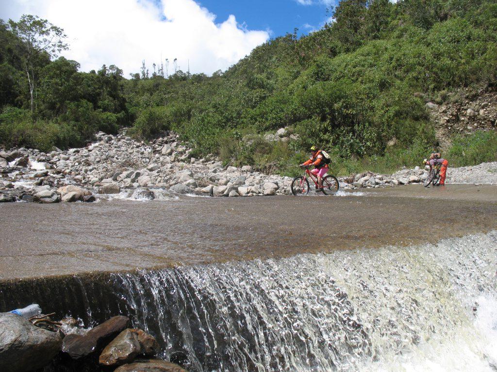 Inca Jungle Trail - Cyclist rides through a river.