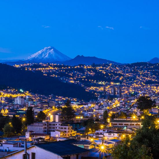 Snow-capped Cotopaxi Volcano with Quito city lights in foreground.